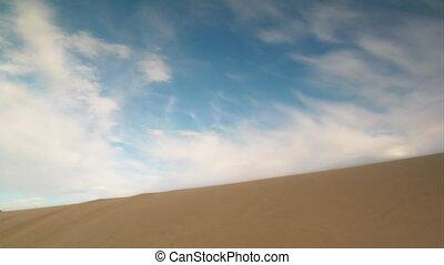 ATV rider jumps sand dune