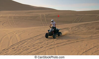 ATV rider jumps sand dune