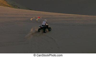ATV rider on sand dune