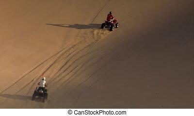 ATV riders climb enormous sand dune