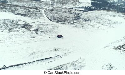 Aerial shooting of ATV vehicle rushes on the snow-covered field and hills