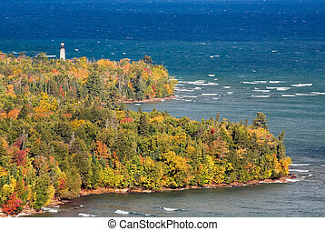 The Au Sable Light Station, surrounded by colorful fall foliage, stands on the Lake Superior shore of Michigan's Upper Peninsula at Pictured Rocks National Lakeshore near Grand Marais.