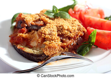 Traditional Italian aubergine parmagiana, a vegetarian eggplant dish, served with sliced tomatoes and garnished with basil.