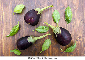 Aubergines and basil leaves on a wooden table