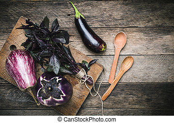 Aubergines with basil and spoons on wooden table. Rustic style and autumn food photo