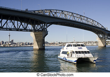 AUCKLAND, NZ - MAY 27 2014:Fullers Ferry sail under Auckland Harbor Bridge. Fullers Group is the latest in a long line of continuous harbour and gulf ferry operations based in Auckland since the 1870s.