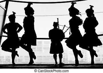 AUCKLAND - JUNE 01 2014:Group of dancers dancing Scottish highland dance in kilts and bagpipe music during Queens birthday in Auckland, New Zealand.