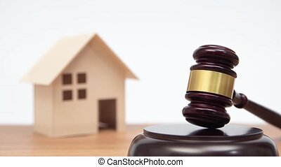 Auction or law concept. Miniature House on wooden table and judge gavel. Zoom out.