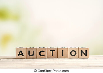 Auction sign on a vintage table on green background