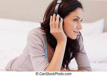 audífonos, mujer, cama, ella