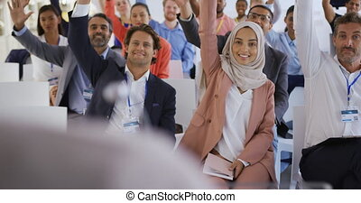 Audience at a business presentation raising their hands to ask questions