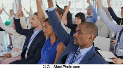 Audience at a seminar raising hands to ask questions