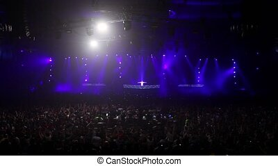 Audience at rave party in large hall with stroboscopic illumination, dj jump on stage