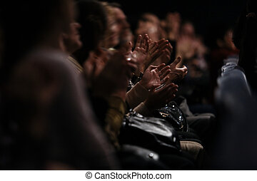 View down a row of people sitting in an audience of people clapping their hands in appreciation of a performance