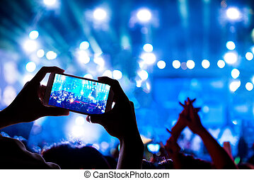 audience crowd with the power of live concert, silhouette hands of people use smart phones enjoying the concert.