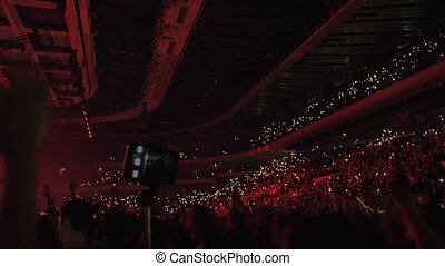 Audience dancing with lights at the concert