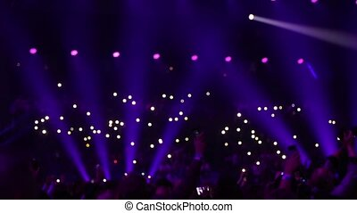 Audience is shining with flashlights of phones. - Concert in...