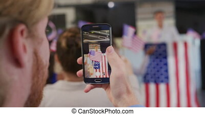 Over the shoulder view of a Caucasian man holding a smartphone and filming a speaker standing on a podium decorated with a US flag at a political rally, and the audience waving flags