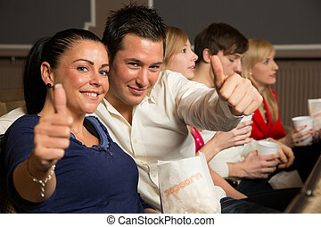 Audience members showing thumbs up - People in a theatre, a...