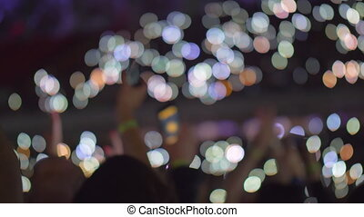 Audience waving with cellphone flashlights at the concert