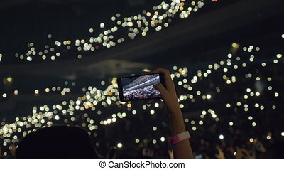 Audience with lights in concert hall and woman taking mobile video