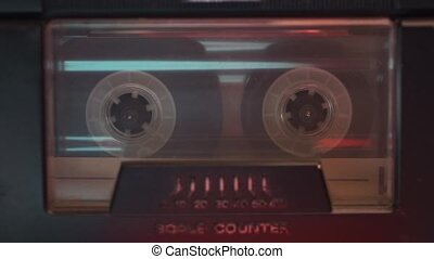 audio cassette inside vintage deck start playing, focus on tape