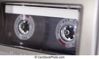 Audio Cassette is inserted into the Deck of the Audio Tape Recorder Playing and Rotates. Macro. Vintage transparent audio cassette tape with a blank label used for sound recording in a retro cassette player. Close-up.