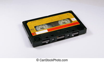 Audio Cassette Rotates on White Background. Vintage Yellow Retro tape cassette with a blank label. Old music. Close-up.
