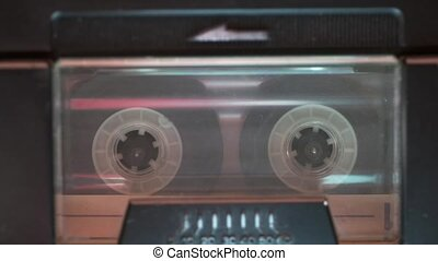 audio cassette start playing inside vintage deck, focus on tape