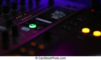 Audio control panel close-up at the concert during the performance. The buttons are lit by different colors.