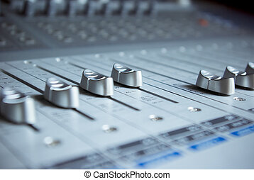 Close up of audio mixing board with several channel volume sliders. Dials are also visible as blur in background.