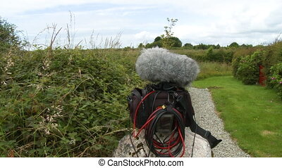 Ab audio bag with a recorder and microphone covered by a dead cat sitting on a rock collecting ambient sound in a field