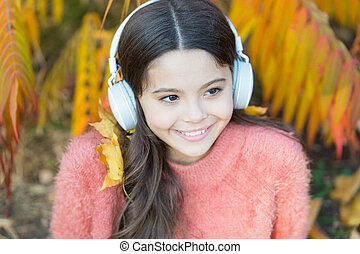 Audio file. Educational podcast. Feel joy. Kid girl relaxing near autumn tree with headphones. Music for autumn cozy mood. Listening song. Autumn playlist concept. Enjoy music outdoors fall warm day