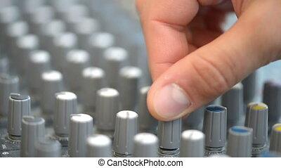 Hand adjusting audio mixer buttons