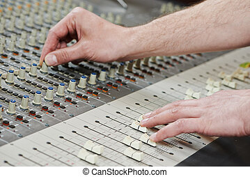 close-up hands of sound engineer work with faders on mixer