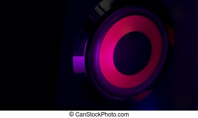 Audio speakers lit by colorful neon club lights. Professional studio subwoofer speaker isolated. Concept for dance music party. Close up. Slow motion