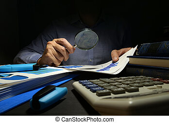 Auditor checks financial report with magnifying glass....