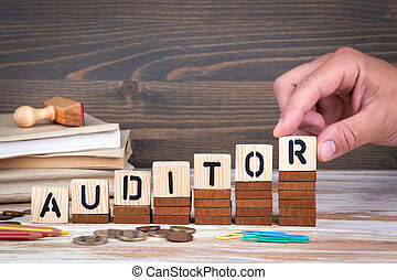 Auditor concept. Wooden letters on the office desk, informative and communication background