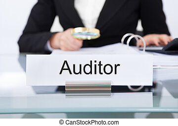 Auditor Scrutinizing Financial Documents - Closeup of uditor...