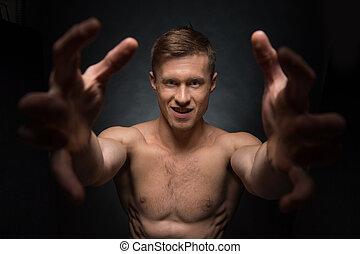 aufschließen, von, anfall, shirtless, mann, dehnen, seine, arme, zu, der, kamera., stehende , und, anschauen kamera, freigestellt, aus, schwarzer hintergrund