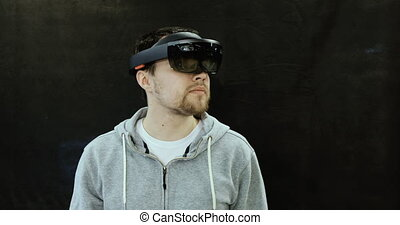 Augmented Reality Glasses. Young adult Caucasian man using holographic augmented reality glasses. Game development.