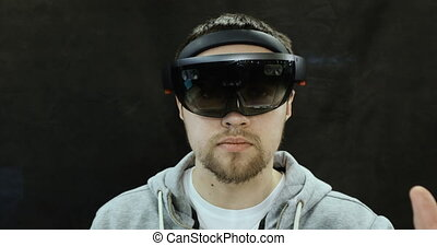 Young man with holographic glasses. Augmented Reality Glasses.