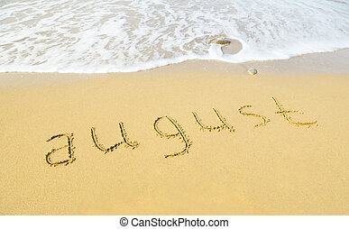August - written in sand on beach texture - soft wave of the sea