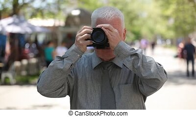 Auld man stands, raises his camera and takes photos in an...