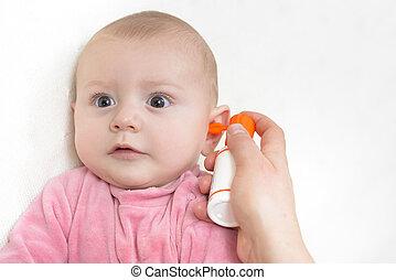 Auricular Hygiene. Woman using ear spray for baby.