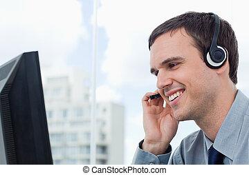 auriculares, sonriente, trabajador, oficina, utilizar
