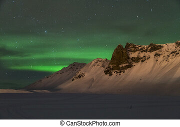 Aurora borealis over the mountains is Iceland