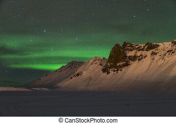 Aurora borealis over the mountains is Iceland