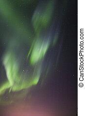 Aurora borealis over town lights glow