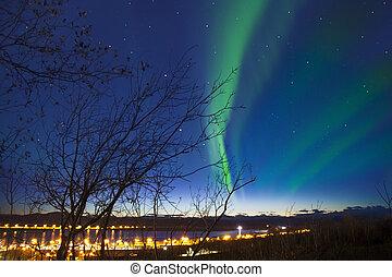 Aurora with the light on the horizon at Kiruna Cityscape,...